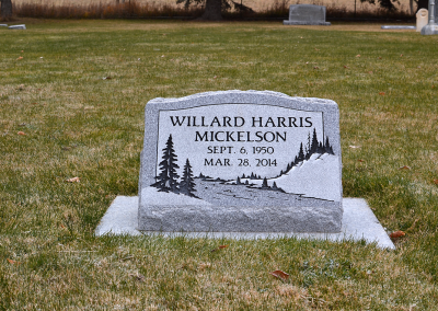 Light grey single person slant headstone on cement foundation