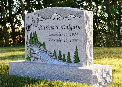 Light grey single person upright headstone with colored mountain and river scene