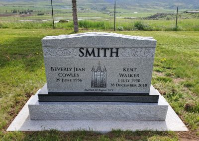 Light grey companion upright headstone with black sub base and engraved SLC temple