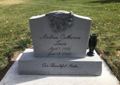 Light grey single person upright headstone with shape carved lilies